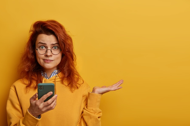 indignant-puzzled-redhead-woman-raises-palm-thinks-what-to-answer-on-received-message-holds-mobile-phone-wears-round-spectacles-and-hoodie-models-over-yellow-wall-with-blank-space-right_273609-42106